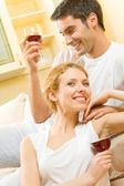 Young couple celebrating with red wine at home — Stock Photo