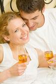 Junges paar feiert mit champagner am zimmer — Stockfoto