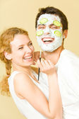 Young happy joyful couple making facial masque at home — Stock Photo