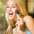 Young happy woman with makeup brush indoors — Stock Photo #6571973