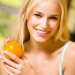 Portrait of young happy smiling woman with orange — Stock Photo #6572279