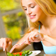 Portrait of young happy smiling woman eating salad — Stock Photo