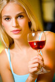 Portrait of young beautiful blond woman with red-wine glass, ind — Stock Photo
