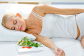 Portrait of young beautiful sleeping woman with gifts on bed at — Stock Photo