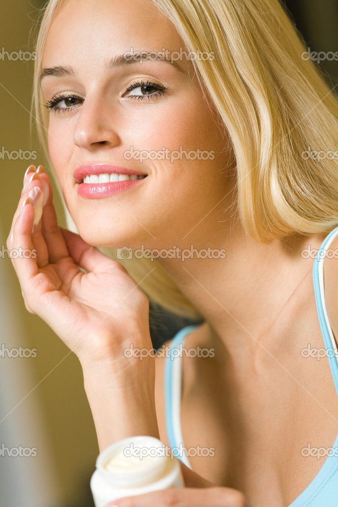 Young happy smiling woman with cosmetic cream at home — Stock Photo #6572075