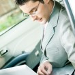 Businessman working with laptop in the car — Stock Photo #6584090