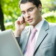 Stock Photo: Business man working with laptop and cellphone, outdoors