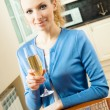 Royalty-Free Stock Photo: Portrait of young woman with glass of champagne, at home