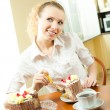 Stock Photo: Young womeating torte at home