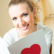 Young happy smiling beautiful woman, reading valentine card at home — Stock Photo