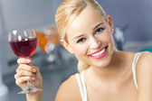 Portrait of young woman with glass of red wine, at home — Stock Photo