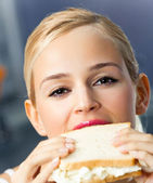 Woman eating sandwich, at home — Foto de Stock