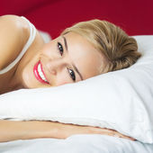 Happy smiling woman waking up at bedroom — Stock Photo