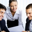 Stock Photo: Three businesspeople working with document at office