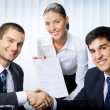 Businesspeople handshaking with document at office — Stock Photo #6653178