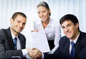 Businesspeople handshaking with document at office — Stock Photo