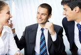 Happy businessman with document and colleagues at office — Stock Photo