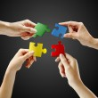 Hands and puzzle on black background — Stock Photo