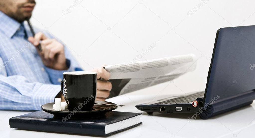 Man at office reading newspaper, with coffee in front — Stock Photo #6302361