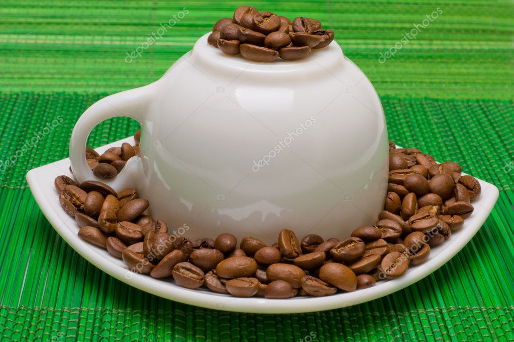Cup and saucer with the coffee beans on a green table-napkin  Stock Photo #6666845