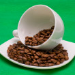 Cup and saucer with the coffee beans on a green background - Stock Photo