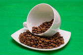 Cup and saucer with the coffee beans on a green background — Stock Photo