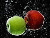 Red and green apples in water — Stock Photo