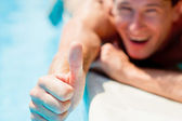 Man showing a thumbs up near swimmingpool — Stock Photo