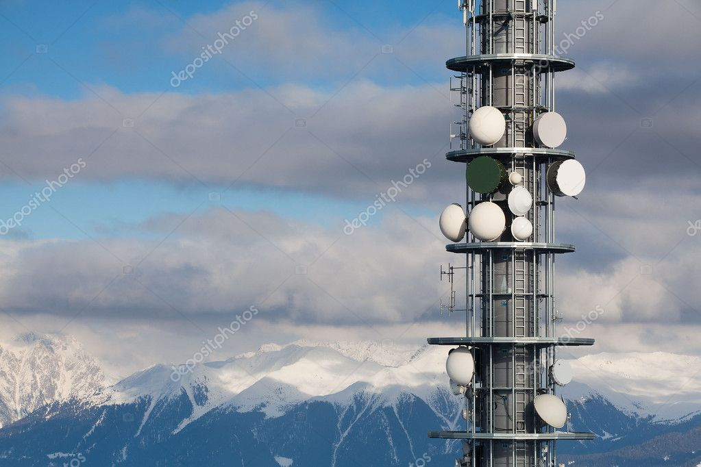 Communication antenna tower and satellite dishes against blue sky — Stock Photo #6356304