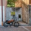 Old italian motorcycle parked in front of stone wall - Stock Photo