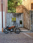 Old italian motorcycle parked in front of stone wall — Stock Photo