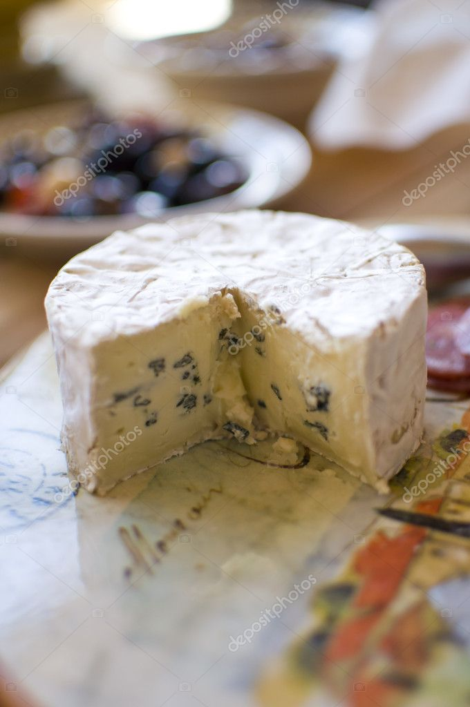Small wheel of bliue brie on a tuscan cutting board — Stock Photo #6376146