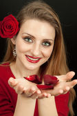 Beautiful girl holding rose petals — Стоковое фото