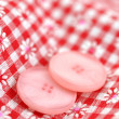 Buttons on Checkered Textile - Stock Photo