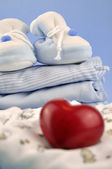Red Heart and Baby Clothes — Stock Photo