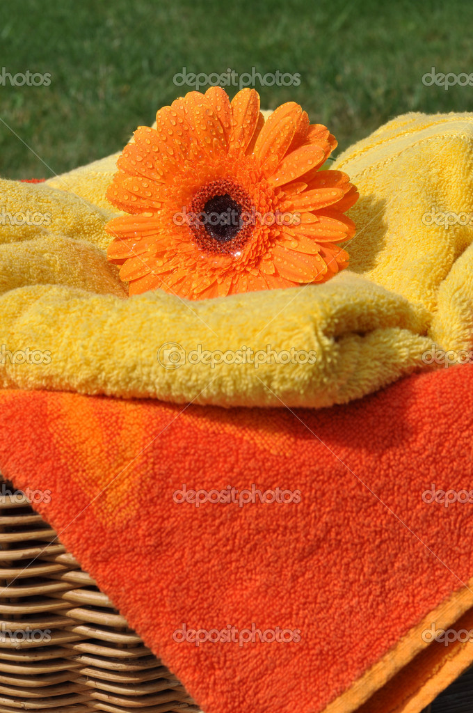 Wet orange gerbera and soft towels in a wicker basket — Stock Photo #6400839
