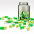 Green-yellow pills in medical bottle with cap — Stock Photo
