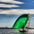 Stock Photo: Sailing Dinghy under cloudy sky