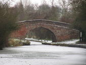Bridge over frozen canal — Stockfoto