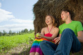 Couple with apples sitting on the grass hay — Stock Photo