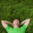 Young man lying on the grass - Stock Photo