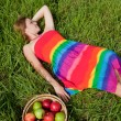 Girl on the grass next to a basket of apples — Stock Photo