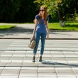 Girl with a bag goes the way of pedestrian zebra — Stock Photo