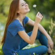 Girl with daisies sits on grass and sniff it — Stock Photo #6497566