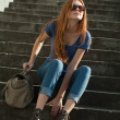 Beautiful red-haired girl sitting on the stairs with a bag — Stock Photo