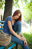 Sad girl sitting on a park bench — Stock Photo