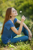 Girl with daisies sits on the grass and sniff it — Stock Photo