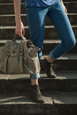 Feet girl holding a bag on the stairs in jeans — Stock Photo