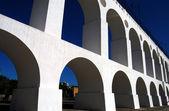 White aqueduct agains blue sky — Stock Photo