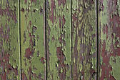 Green paint peeling from a wooden panel door — Stock Photo